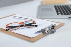 白色桌面特写镜头有膝上型计算机、玻璃、咖啡杯、笔记薄和其他项目的在模糊的城市背景 库存图片