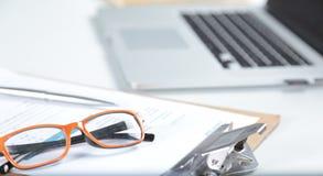 白色桌面特写镜头有膝上型计算机、玻璃、咖啡杯、笔记薄和其他项目的在模糊的城市背景 免版税图库摄影