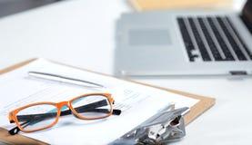 白色桌面特写镜头有膝上型计算机、玻璃、咖啡杯、笔记薄和其他项目的在模糊的城市背景 图库摄影
