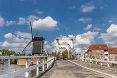 白色桥梁和历史的风车在一条运河在莱顿 免版税库存图片