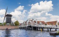 白色桥梁和历史的风车在一条运河在莱顿 免版税图库摄影