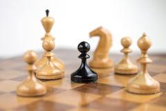 白色棋子围拢的黑典当 免版税图库摄影