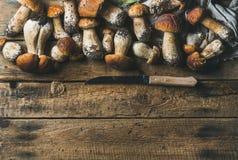白色森林蘑菇和刀子在土气木背景 库存图片