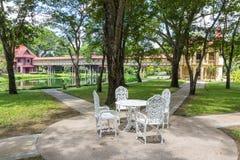 白色椅子和桌在庭院里 免版税库存照片