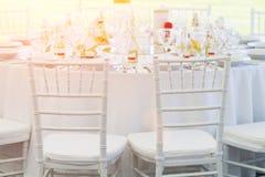 白色椅子和花梢桌为结婚宴会设置了 库存照片