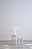 白色椅子在一间空的屋子 免版税库存图片