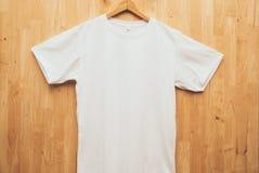 白色概念想法木后面地面正面图的短袖T恤杉简单的回合脖子嘲笑 免版税库存照片