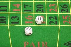 白色模子的卷在一个比赛表上的在赌博娱乐场 图库摄影