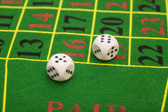 白色模子的卷在一个比赛表上的在赌博娱乐场 库存图片