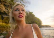 白色比基尼泳装和牛仔布短裤的年轻美丽和性感的妇女放松在美好的热带天堂海滩和岩石背景 库存照片