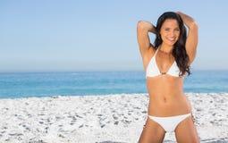白色比基尼泳装摆在的微笑的性感的妇女 库存图片