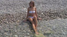 白色比基尼泳装的可爱的被晒黑的妇女坐天蓝色的海的有卵石花纹的岸 影视素材