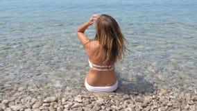 白色比基尼泳装的好被晒黑的妇女坐天蓝色的海的有卵石花纹的岸 股票录像
