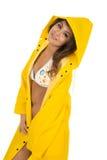 白色比基尼泳装的妇女在黄色雨衣边神色 免版税库存图片