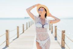 白色比基尼泳装的年轻秀丽微笑妇女,在possing在海背景的码头的帽子和太阳镜 免版税图库摄影