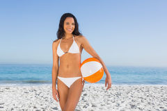 白色比基尼泳装的快乐的性感的浅黑肤色的男人有海滩球的 免版税库存照片