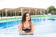 白色比基尼泳装的性感的浅黑肤色的男人在被晒黑的微小和匀称身体是松弛在游泳池 夏天职业 免版税库存照片