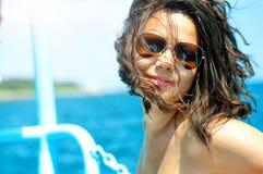 白色比基尼泳装的年轻性感的妇女享用日落和太阳的 免版税库存图片