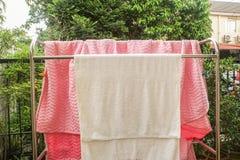 白色毛巾和桃红色毯子在洗涤在阳光下在不锈的晒衣架以后房子外 库存图片
