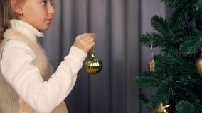 白色毛皮夹克的女孩讲话与某人 女孩装饰圣诞树 女孩装饰hange的金子 股票视频