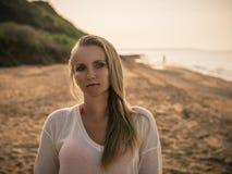 白色毛线衣和红色泳装的美丽的妇女在晚上海的岸 免版税图库摄影