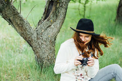 戴白色毛线衣和黑帽会议在开花的庭院里 豆杆 库存图片