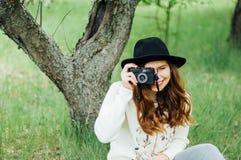 戴白色毛线衣和黑帽会议在开花的庭院里 豆杆 图库摄影