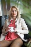 白色毛线衣的可爱的性感的金发碧眼的女人在拿着一杯咖啡的桃红色女衬衫 肉欲的妇女开会画象  库存图片