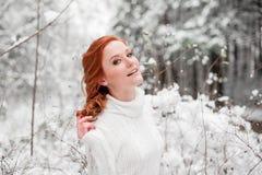 白色毛线衣的姜可爱的女性在冬天森林雪12月在公园 画象 圣诞节逗人喜爱的时间 库存图片