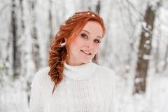 白色毛线衣的姜嫩女孩在冬天森林雪12月在公园 背景圣诞节关闭红色时间 库存照片
