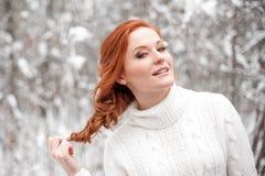 白色毛线衣的姜欧洲女孩在冬天森林雪12月在公园 背景圣诞节关闭红色时间 免版税库存照片