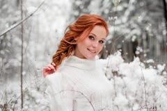 白色毛线衣的姜甜女孩在冬天森林雪12月在公园 画象 圣诞节逗人喜爱的时间 免版税库存照片