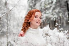 白色毛线衣的姜美丽的女性在冬天森林雪12月在公园 画象 圣诞节逗人喜爱的时间 免版税库存照片