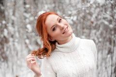 白色毛线衣的姜逗人喜爱的女孩在冬天森林雪12月在公园 背景圣诞节关闭红色时间 免版税库存照片
