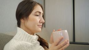 白色毛线衣的年轻女人在家坐沙发和和饮用的咖啡 股票录像