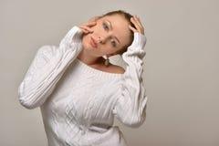 白色毛线衣的美丽的妇女在演播室 免版税图库摄影