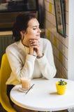 白色毛线衣的美丽的深色的妇女在咖啡馆饮用的咖啡 咖啡馆行家白色和黄色内部  库存图片
