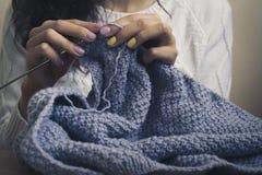 白色毛线衣编织蓝色螺纹的女孩 图库摄影