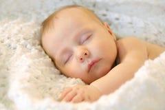 白色毯子的睡觉的新出生的女婴 免版税库存图片