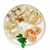 白色汤用海鲜、枪乌贼、虾和鱼在一块板材在白色背景 库存图片