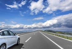 白色汽车在高速高速公路驾驶 免版税库存照片