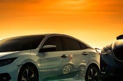 白色汽车正面图有豪华和现代设计的停放在与美丽的橙色和金黄日落天空的停车场 ?? 库存照片
