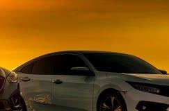 白色汽车正面图有豪华和现代设计的停放在与美丽的橙色日落天空的停车场   免版税库存照片