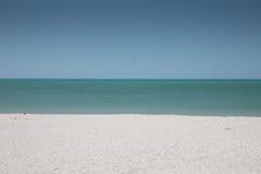 白色沙子、蓝天和绿松石海 库存照片