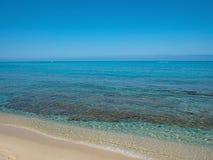 白色沙子海滩由透明海水洗涤了 免版税库存照片