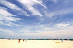 白色沙子海滩和蓝天的打鸣的人 图库摄影