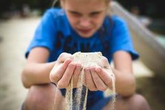 白色沙子通过手指倾吐 库存照片