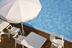 白色沙滩伞和游泳池 免版税库存图片