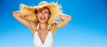 白色泳装和草帽的微笑的妇女在沙滩 库存图片