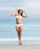 白色泳装的一名年轻深色的妇女在海滩 免版税库存照片